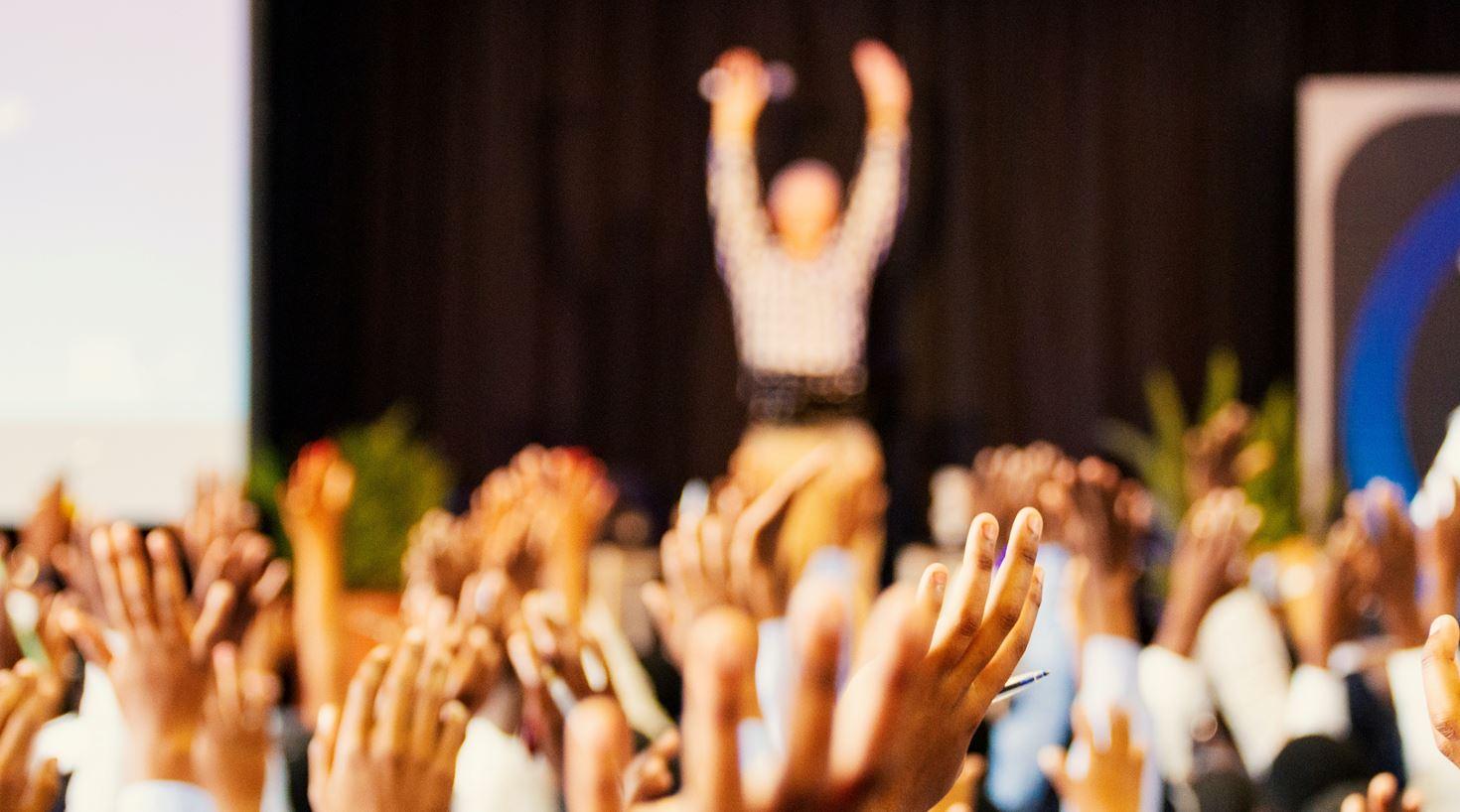 En stor gruppe mennesker er samlet og strekker armene i været fordi de deltar på CX-workshops i kundebegeistring.