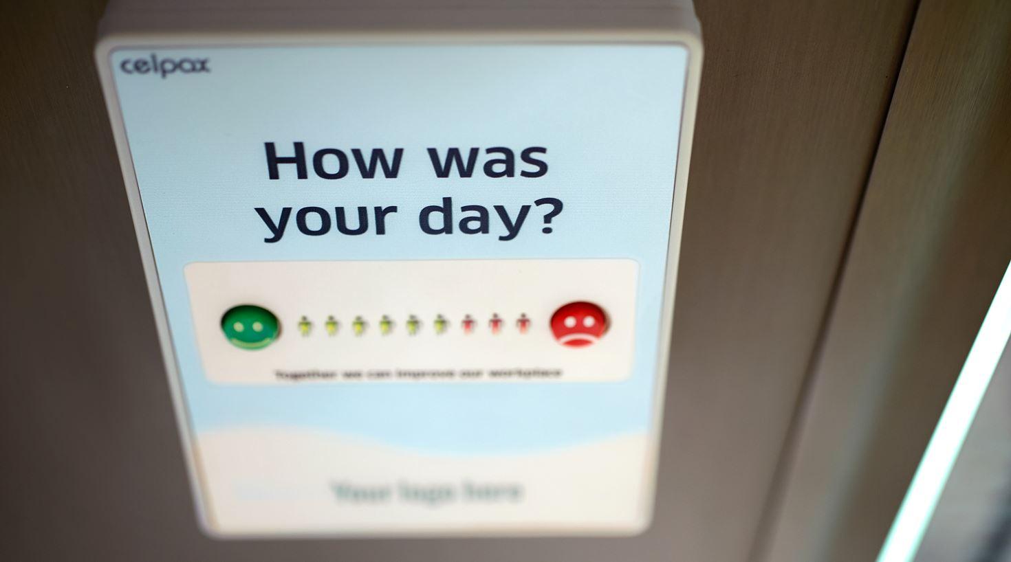 Kvinne gir tilbakemelding på sin kundetilfredshet ved hjelp av Smiley-symboler på en skjerm.