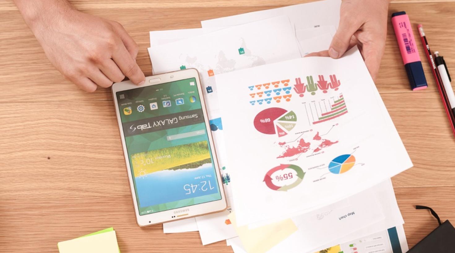 Person tar i bruk både telefon og ulike utskrevet data for å skaffe seg oversikt over hvilke KPI-er som er viktige for å forbedre kundeopplevelsen i bedriften